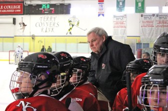 NCHS varsity hockey coach Bo Hickey looks on as New Canaan stuns Darien in March to win the FCIAC hockey crown. Credit: Terry Dinan