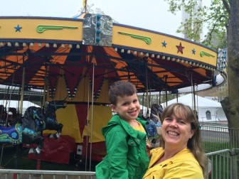 "1985 New Canaan High School graduate Karen (Corker) Malner and her grand nephew Dylan Laviola, 4, both of New Canaan. Dylan heard at school that it would be ""stormy"" on Saturday (the May Fair runs rain or shine), which gave Karen a chance to relive a tradition from her Parade Hill Road childhood: Scope out the rides ahead of time. Credit: Michael Dinan"