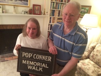"Sandra Conner Lefler and her husband, Mark, with the original William B. ""Pop"" Conner sign that once stood in the path between what is now Saxe Middle School (it was the high school back then) and Conner Field, named for her grandfather. Credit: Michael Dinan"