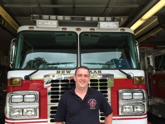 Newly recruited Lateral Firefighter Damien Sheerin stands in front of one of the firehouse's newest rigs.