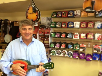 New Canaan Music owner, Phil Williams, strums out a few chords on a watermelon ukelele.