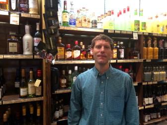 Alex Stewart stands behind the counter inside Walter Stewart's Spirit Shop.