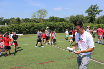 NCHS assistant coach Chris Silvestri checks out the camp itinerary. (Terry Dinan photo)