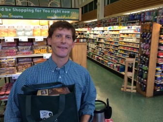 """Alex Stewart of Walter Stewart's market on Elm Street shows us a sample of a pre-packaged bag for the New Canaan Food Pantry. One way to enter next Thursday Aug. 1's """"Taste of the Town Stroll"""" is to purchase a $15 or $25 bag of goods to be donated (and transported by Stewart's) to the New Canaan Food Pantry. Just bring your receipt for the items to a registration table at 6 p.m. on Aug. 21. Credit: Michael Dinan"""