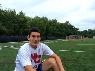 Rising senior Ryan Callahan  ties his cleats before a preseason soccer camp at St. Luke's School's turf field.