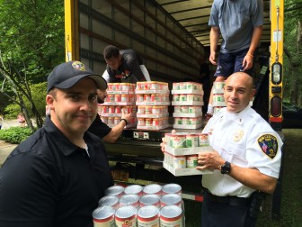 Sgt. Andrew Walsh and Lt. Jason Ferraro of the New Canaan Police Department Special Response Team, making time to lend a hand at the Filling in the Blanks unloading Thursday. Credit: Michael Dinan