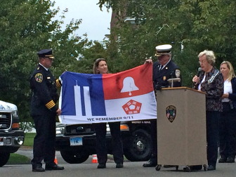 """L-R: Police Chief Leon Krolikowski, EMT Wendy Hilboldt and Fire Chief Jack Hennessey receive a """"flag of remembrance"""" from Diane Wells of New Canaan's Hannah Benedict Carter Chapter of the Daughters of American Revolution on Sept. 11, 2014 in front of NCPD. The flag will hang beside the 9/11 memorial at the fire house. Credit: Michael Dinan"""