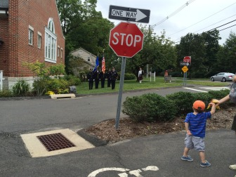 A boy holds his mom's hand as the NCPD Honor Guard passes, placing a memorial wreath in front of the New Canaan Volunteer Ambulance Corps building on South Avenue during a Sept. 11 memorial ceremony, held Sept. 11, 2014. Credit: Michael Dinan