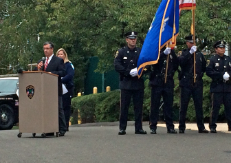 Kelly Daniel stands near First Selectman Rob Mallozzi, at the podium and standing near the New Canaan Police Department Honor Guard—composed of Officers Jeff Deak, Chris Dewey, Aaron LaTourette and Jason Kim and led by Police Capt. Vincent DeMaio—during a Sept. 11, 2014 memorial service. Credit: Michael Dinan
