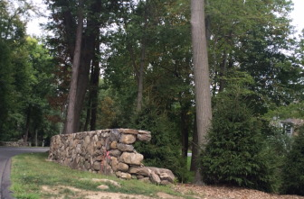 The Kekedjians of 309 Lukes Wood Road are seeking to purchase from the town some of the property in front of their house in order to extend a stone wall that is designed to keep kids safely away from the road. Credit: Michael Dinan