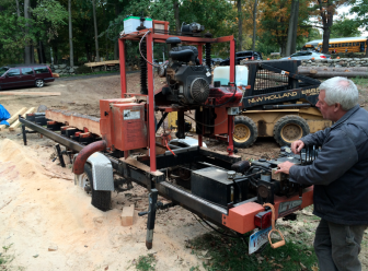 George Bell saws the Larsons' trees into usable-size pieces of lumber for a barn restoration. Credit: Michael Dinan