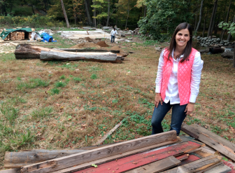 Kristina Larson stands near five piles of salvaged original wood from the ca. 1910 barn her family is restoring on their Ponus Ridge property. Credit: Michael Dinan