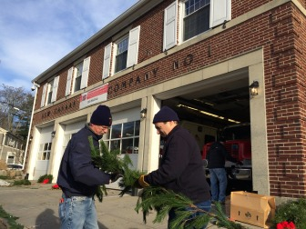 New Canaan firefighters Sven Englund (L) and Mark Savini (R) wrap the white pine roping in lights prior to looping it, according to local tradition, below the roofline of the firehouse at Main and Locust. It's done on the first Sunday of December each year—in 2014, that's Dec. 7. Credit: Michael Dinan