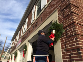 Longtime volunteer firefighter, New Canaan First Selectman Rob Mallozzi, hangs a wreath as part of the annual decorating at the firehouse. The first Sunday of December this year was Dec. 7, 2014. Credit: Michael Dinan