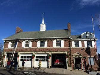 New Canaan firefighters deck the firehouse at Main and Locust on Dec. 7, 2014—an annual tradition that goes back as long as locals remember, likely to when the structure was built in 1938. Credit: Michael Dinan