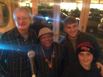 """Minutes before a jamming session at a jam-packed Chef Luis on Thursday night. L-R: Peter """"The Bushman"""" Bush of FOX 95.9 FM, Paul Simon bassist Bakithi Kumalo, New Canaan Music owner Phil Williams and his son, Bailey. Credit: Michael Dinan"""