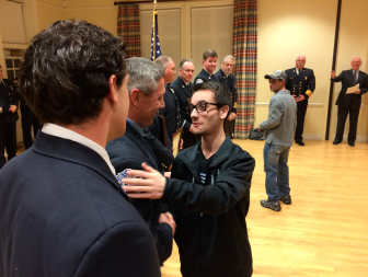 Michael Bivona, Jr., 18, greets Firefighter Paul Wilson during the Jan. 13, 2015 ceremony at Lapham Community Center where eight New Canaan firefighters received a unit citation for helping to save the teen's life in the aftermath of a horrific four-car crash on Oct. 30. Credit: Michael Dinan