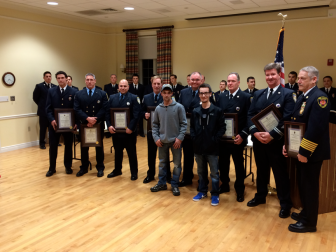 Michael Bivona, Sr. and his son, 18-year-old Michael Bivona, Jr. stand in front of the eight New Canaan firefighters who helped save the younger man's life following a horrific Oct. 30 car crash on Silvermine Road. Presented Jan. 13, 2015 with a unit citation during a ceremony at Lapham Community Center, those men are (L-R): Firefighter Jason DeVivo, Firefighter Paul Wilson, Firefighter John Aniello, Firefighter Dave DiPanni, Firefighter Jim Pickering, Lt. Tony Ryan, Capt. John Raidt and Firefighter Edward Karl. Credit: Michael Dinan
