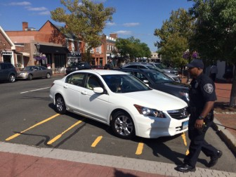 NCPD Community Impact Officer Roy Adams on Sept. 15 instructs an illegally parked motorist to back out of non-spot on Elm Street. The town has since installed bollards in the spot, and motorists now can be seen parking directly in the crosswalk where Adams is standing in this photo. Credit: Michael Dinan