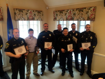 """Pictured L-R, recipients of a Unit Citation on March 26, 2015, New Canaan Police Department Officers Thomas Callinan, Marc DeFelice, Brian Mitchell, Geoffrey Lambert, Jason Kim, Thomas Patton and Aaron LaTourette. Capt. Vincent DeMaio in recognizing the group said that after Patton went a step beyond what's normally required to investigate a report of a suspicious package delivered in January to a Knapp Lane home, the other members of the day shift participated in important ways in driving an investigation that ended up identifying the nexus of a national criminal organization: """"This was an organized criminal gang, located out of the Bronx. They would use stolen credit cards to purchase cellphones, they would always take the insurance on them,  then get the cellphones and claim they had never received them because they were sent to fraudulent addresses. Then they would take the insurance and get another cellphone, so it was two-for-one. A stolen credit card buys you two phones instead of one. Through detailed investigation we were able to learn that this was pretty much a scheme that was occurring all the way up and down the East Coast."""" Credit: Michael Dinan"""