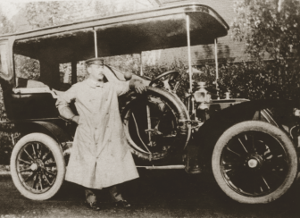 """A Lapham family chauffeur stands by a motor vehicle by the Carriage Barn near Waveny House in the early-1900s. The Carriage Barn now is home to an arts center and gallery, and an upcoming exhibition, """"Va Va Vroom,"""" and fundraiser event, """"Monaco Grand Prix,"""" will pay homage to that heritage. Photo courtesy of Carriage Barn Arts Center"""