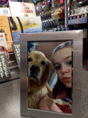This photo of Tango and Grace lives behind the counter at Mackenzie's. The selfie was taken nine months ago and Tango, a 7-year-old golden retriever, passed suddenly and unexpectedly last month. Credit: Michael Dinan