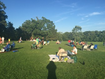 Residents begin to set up their picnics for this week's summer concert. Credit: Bella Carpi