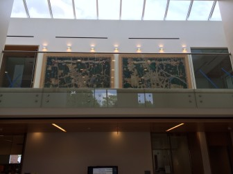 A pair of 78-by-115-inch WPA paintings by Walter Bradnee Kirby that imagined aerial views of New Canaan in 1834 and 1934, respectively, are being showcased under the skylight of the addition at Town Hall. Credit: Michael Dinan