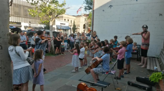 Kids from the Talent Education Suzuki School (TESS) of Norwalk playing out front of Baskin Robbins on a recent Friday evening. Contributed