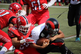 James Freyre (#26) with a tackle during New Canaan's 53-8 win over Central, September 26, 2015. Credit: Terry Dinan