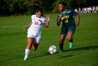 Junior Paige Freyre pushing the ball upfield past Trinity defender Tiara Starks.