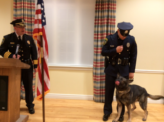 "NCPD K-9 dog Apollo gets his ""badge"" during a department awards and promotion ceremony on Sept. 15, 2015 in the Douglass Room at Lapham Community Center. He's pictured here with Police Chief Leon Krolikowski (L) and his handler, Officer David Rivera. Credit: Michael Dinan"