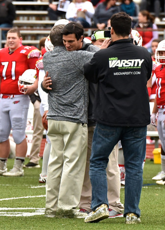 Lou and John Marinelli embrace prior to meeting on the field as coaches for opposing teams for the first time—Oct. 24, 2015 at Greenwich High School. Chris Cody photo