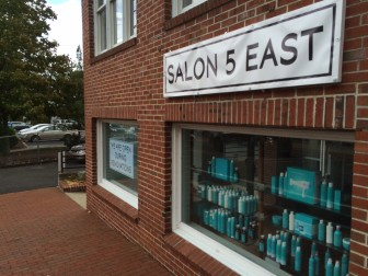 Salon 5 East has hung a temporary new sign outside the salon and spa near the corner of East Avenue and Main Street. Credit: Michael Dinan