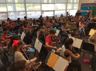 "The 6th Grade Orchestra (56 students) playing ""Wexford Circle"" in a 909-square-foot room. That's 13 square feet per student versus a state recommendation of 32. Credit: Greg Macedo"