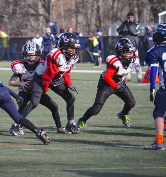 """New Canaan QB Chris Ippolito follows blocks from the """"Big Ben's"""" - center Benj Michels and guard Ben Sibbett - on a way to a big gain. Credit: Contributed"""