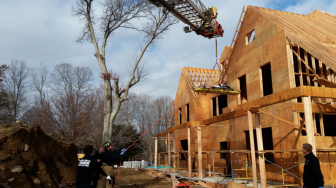 Emergency responders lower a man from the second floor of a home under construction on Carter Street. There were no stairs at the home, where the victim fell one floor, officials said. Photo published with permission from its owner