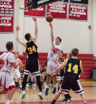 Jack Richardson launches a lay-up, also pictured for New Canaan are Stepen Wronski and CJ D'Virgilio. Credit: Mike Wilson