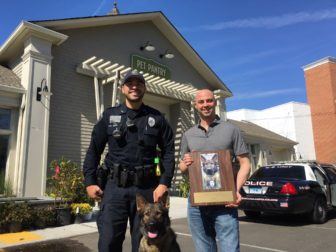 New Canaan Police K-9 Officer David Rivera and Pet Pantry Owner Adam Jacobson stand with K-9 dog Apollo in front of the pet shop on Grove Street in New Canaan. Credit: Michael Dinan