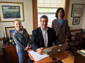 NCHS senior interns (for New Canaanite) Emilia Savini and John Bemis stand on either side of First Selectman Rob Mallozzi in his office, at a new stand-up desk. Credit: Michael Dinan