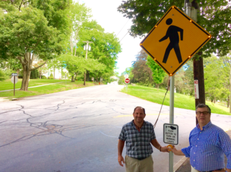 Tiger Mann (L) and Rob Mallozzi (R) at the new flashing sign that now faces northbound Park Street motorists when a pedestrian seeking to cross at God's Acre pushes a button. Another sign warns drivers traveling up the hill along St. John's Extension. Credit: Michael Dinan