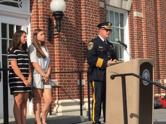 "New Canaan Police Chief Leon Krolikowski addresses a small crowd gathered out front of Town Hall on Sept. 9, 2016 during a memorial service for those lost during the Sept. 11, 2001 terrorist attacks. The police chief said during his remarks that those who have given their lives for the United States during the subsequent War on Terror also are remembered. He is joined on the front steps of Town Hall in this photo by New Canaan High School juniors Caroline Callahan and Cassidy Little, who sang a lovely rendition of ""God Bless America."" Credit: Michael Dinan"