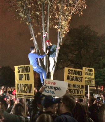 Chase Williams, NCHS '14, in the red hat, up a tree outside the White House before dawn on Nov. 9, 2016, in the hours after GOPer Donald Trump won the presidential race. Published with permission from its owner.